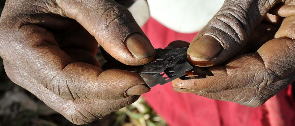 Prisca Korein, a 62-year-old traditional surgeon, holds razor blades before carrying out female genital mutilation on teenage girls from the Sebei tribe in Bukwa district, about 357 kms (214 miles) northeast of Kampala, December 15, 2008. The ceremony was to initiate the teenagers into womanhood according to Sebei traditional rites. REUTERS/James Akena