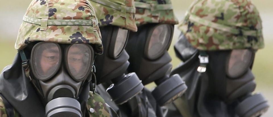 Personnel from Japan's Self-Defense Forces in protective gear take part in an NBC exercise in Chitose, Japan