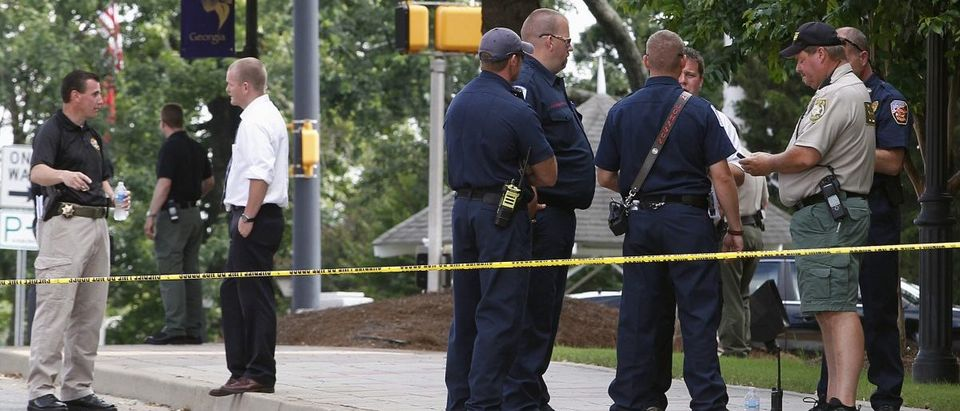 Police officers along with Forsyth County sheriff deputies investigate the scene at the Forsyth County Courthouse following a shooting incident in Cumming, Georgia June 6, 2014. A man armed with an assault rifle and explosives who drove up to the courthouse on Friday and shot and wounded a sheriff's deputy in the leg was killed in a shootout with authorities, officials said. The suspect, Dennis Marx, pulled his silver sport utility vehicle to the front of the courthouse and was immediately confronted by a sheriff's deputy, Forsyth County Sheriff Duane Piper told reporters. Marx had been engaged in a legal dispute with the county sheriff's department. REUTERS/Tami Chappell