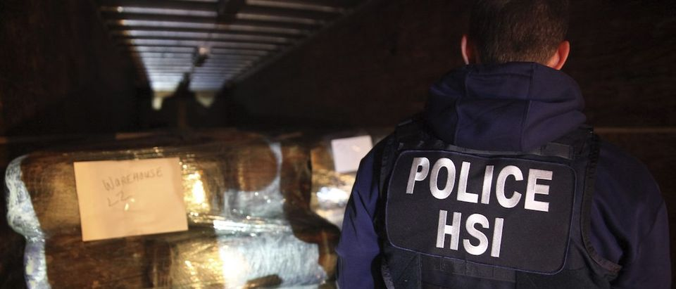 Handout shows a Homeland Security special agent examining seized drugs in a highly sophisticated tunnel used to smuggle drugs between the U.S. and Mexico