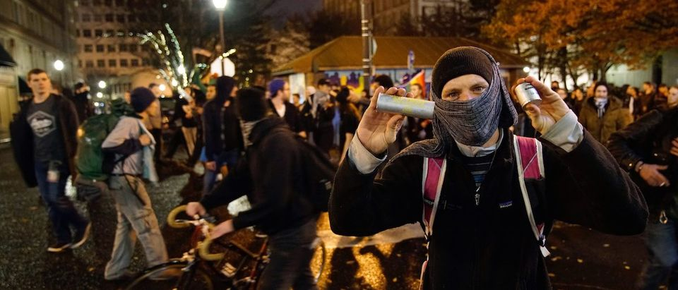 A demonstrator holds up cartridges during a protest against the election of Republican Donald Trump as President of the United States in Portland, Oregon