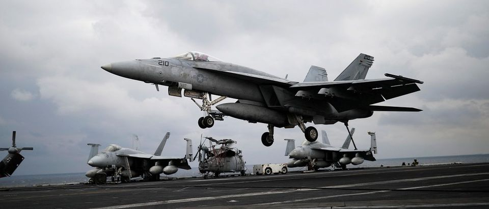 """A U.S. F18 fighter jet lands on the deck of U.S. aircraft carrier USS Carl Vinson during an annual joint military exercise called """"Foal Eagle"""" between South Korea and U.S., in the East Sea"""