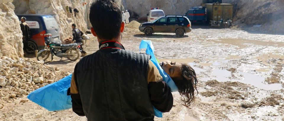 A man carries the body of a dead child, after what rescue workers described as a suspected gas attack in the town of Khan Sheikhoun in rebel-held Idlib