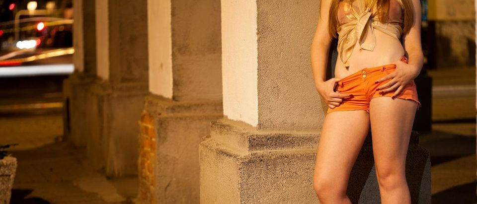 Prostitute leaning against a pillar waiting for a client. Photographee.eu/Shutterstock.
