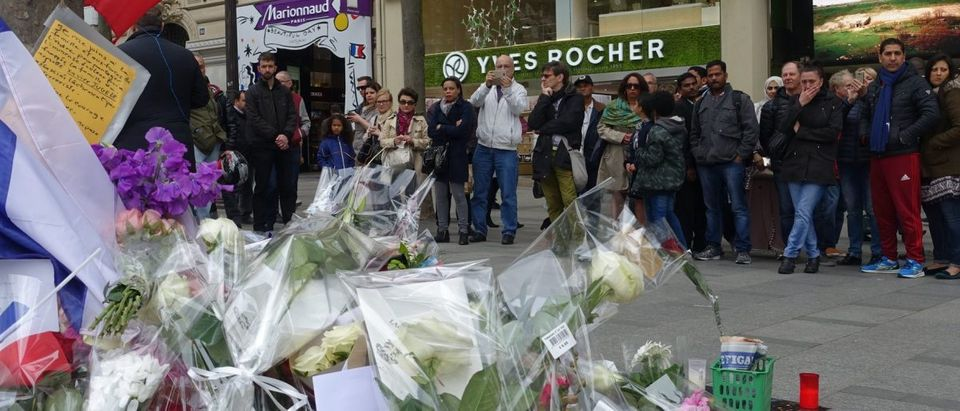 Parisians and tourists pay their respects at the scene of Thursday's terror attack, which claimed the life of a police officer. (Jacob Bojesson/TheDCNF)