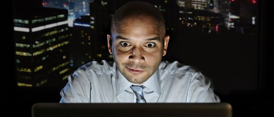 Addict businessman alone at night sitting at office computer laptop watching porn, online gambling or working late in addiction concept (Shutterstock/Marcos Mesa Sam Wordley)