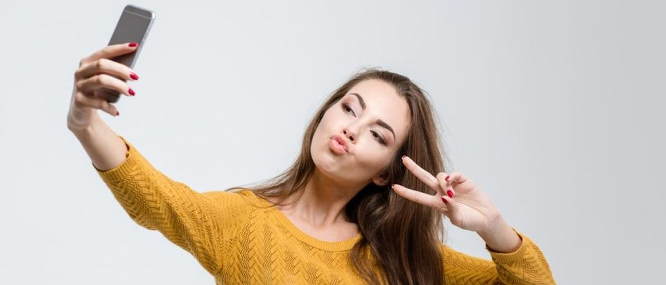 Young attractive woman taking a selfie on her smartphone. [Shutterstock- ESB Professional]