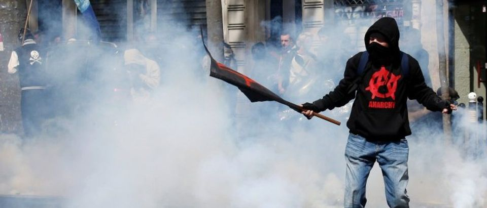 A masked demonstrator protects himself from tear gas during clashes at the traditional May Day labour union march in Paris