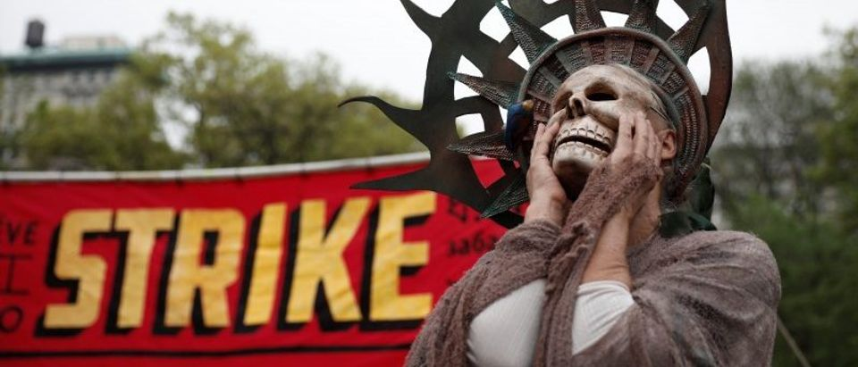 A woman wearing a costume stands during a May Day protest in New York