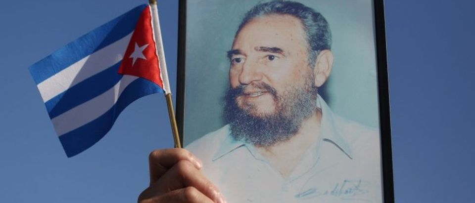 A man holds a picture of Cuba's late President Fidel Castro during a May Day rally in Havana