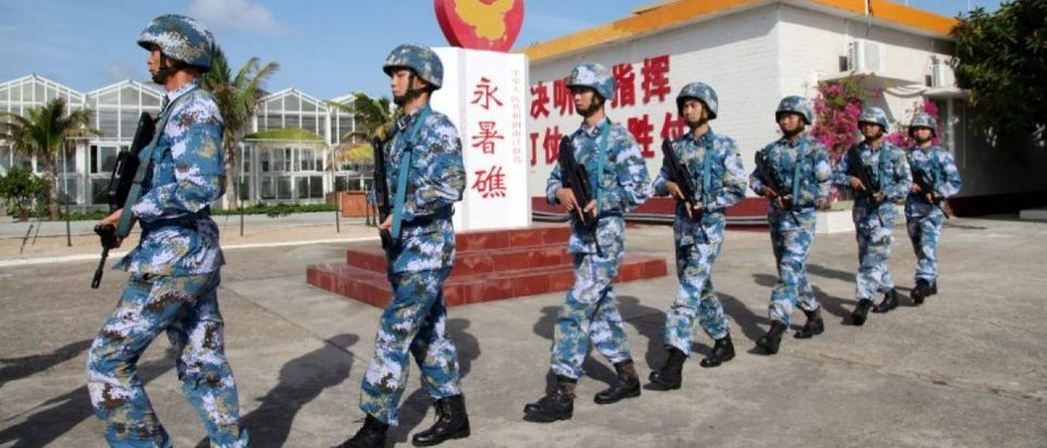 FILE PHOTO: Soldiers of China's People's Liberation Army (PLA) Navy patrol at Fiery Cross Reef, in the Spratly Islands, known in China as the Nansha Islands