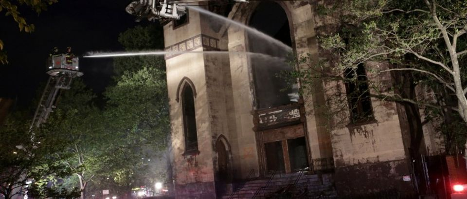 FILE PHOTO: Firemen spray the burned Beth Hamedrash synagogue in New York City