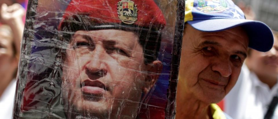 A government supporter holds up a photograph of Venezuela's late President Hugo Chavez during a rally in support of Venezuela's President Nicolas Maduro in Caracas