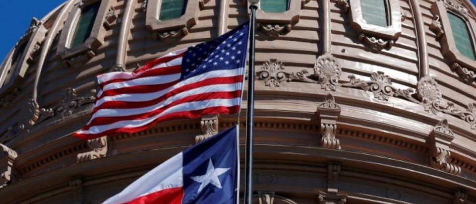 FILE PHOTO - The U.S flag and the Texas State flag fly over the Texas State Capitol in Austin