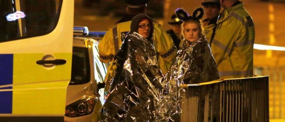 Two women wrapped in thermal blankets stand near the Manchester Arena, where U.S. singer Ariana Grande had been performing, in Manchester, northern England, Britain