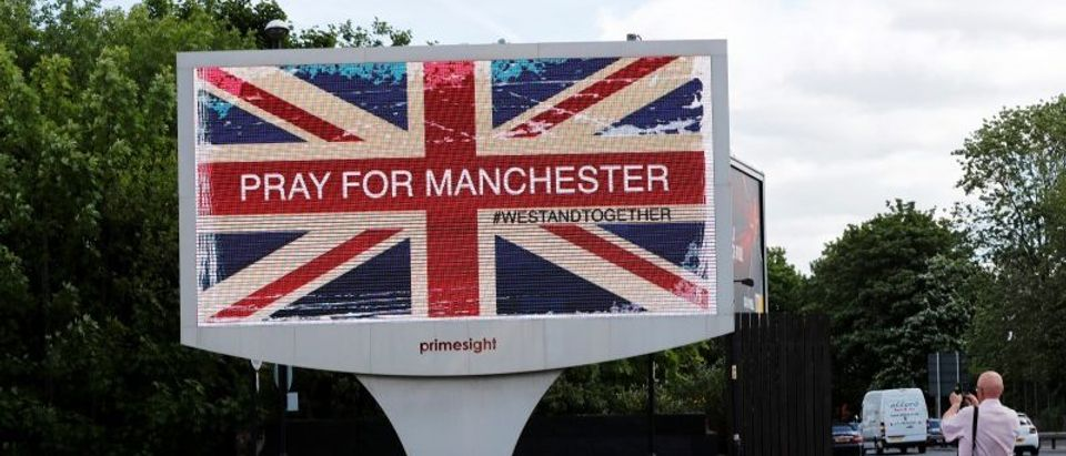 A man photographs a sign in Manchester