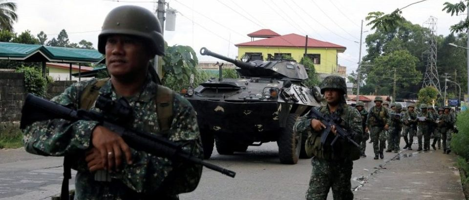 Philippine Marines walk next to AFV as they advance their positions in Marawi