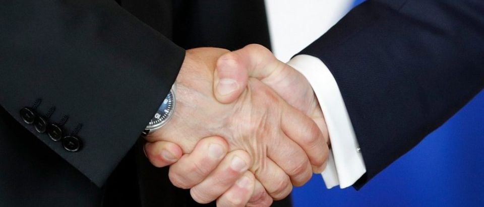 French President Emmanuel Macron shakes hands with Russian President Vladimir Putin at the Chateau de Versailles as they meet for talks before the opening of an exhibition marking 300 years of diplomatic ties between the two countries in Versailles