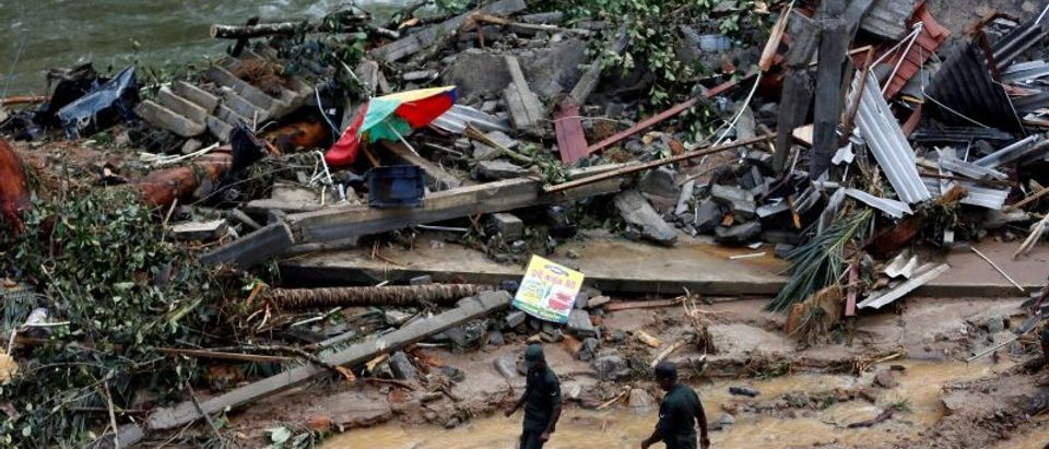 Sri Lankan army soldiers walk past the debris of houses at a landslide site during a rescue mission in Athwelthota village, in Kalutara