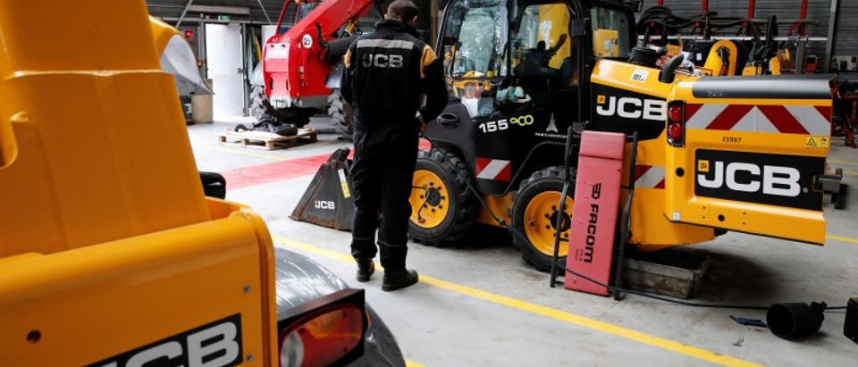 An employee works on a skid steer loader manufactured by JC Bamford Excavators Ltd. at the JCB France headquarters in Sarcelles