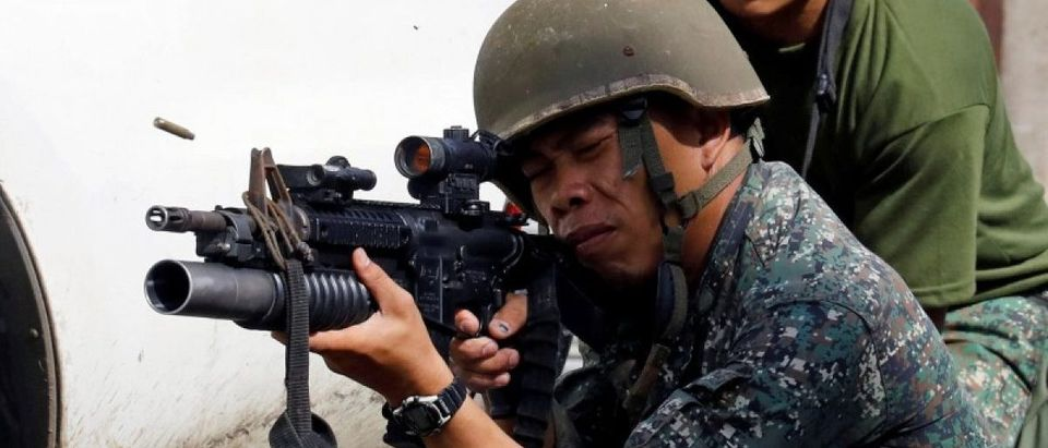 A Philippine Marine fires his weapon towards the stronghold of Maute group in Marawi City