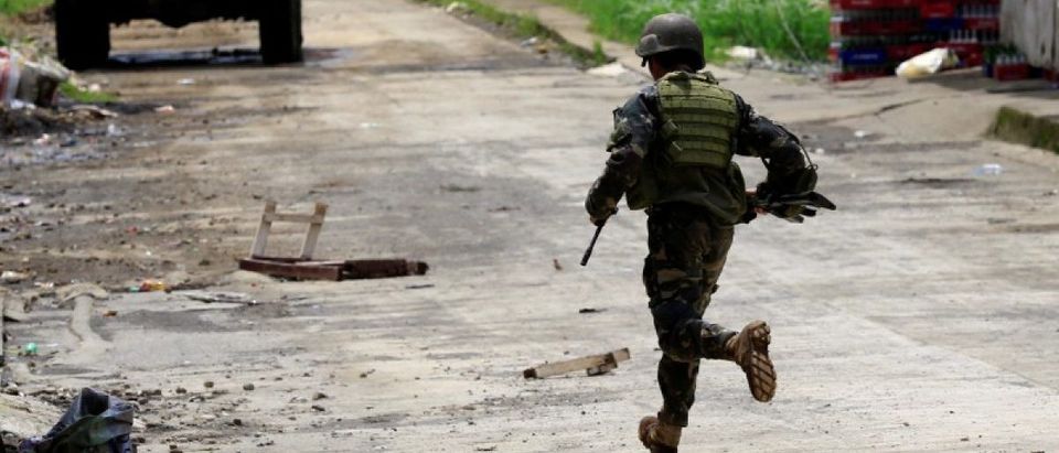 A government soldier runs towards his colleague during government troops assault with insurgents from the so-called Maute group, who have taken over large parts of the Marawi city