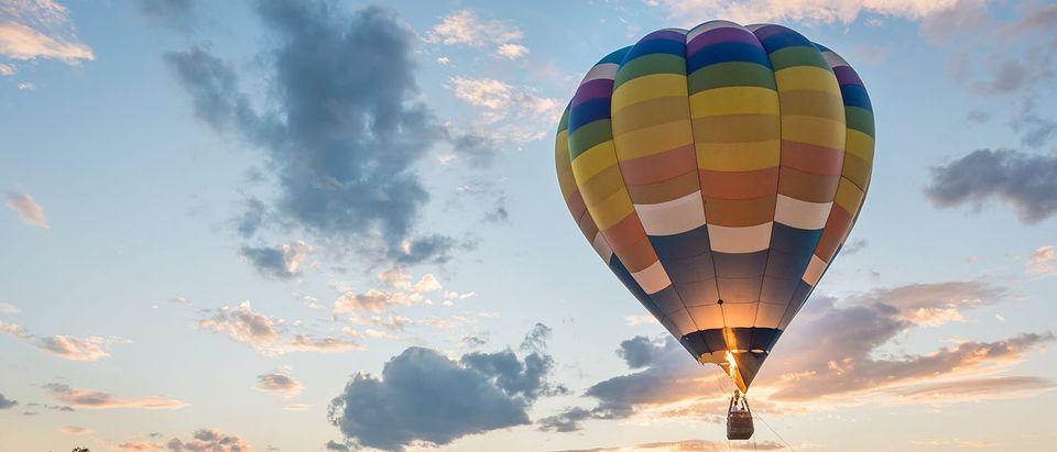 A hot air balloon flies at sunrise. (pongpinun traisrisilp/Shutterstock)