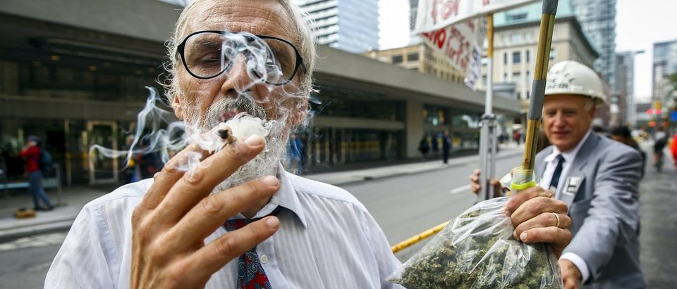 Activist Ray Turmel holds a bag of medical marijuana as he smokes a marijuana cigarette outside the building where the federal election Munk Debate on Canadas Foreign Policy is being held in Toronto