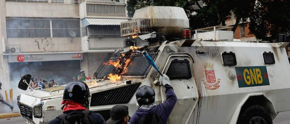 Opposition supporters clash with riot police during a rally against President Nicolas Maduro in Caracas