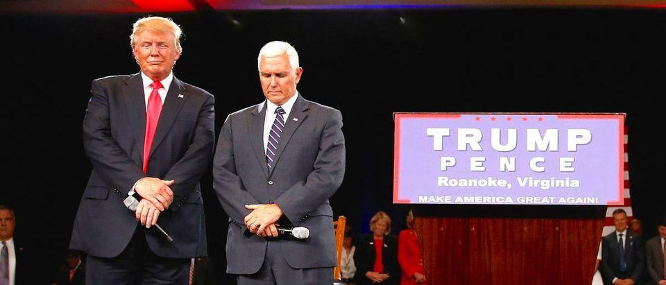 Republican presidential candidate Donald Trump and vice presidential candidate Mike Pence pray at a campaign event in Roanoke
