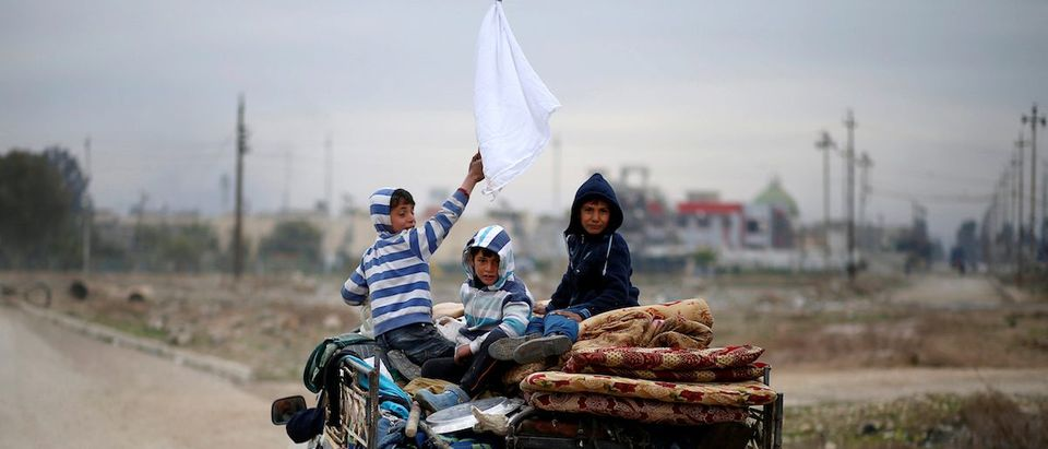 A displaced Iraqi boy holds a white flag as his family flees during the battle between Iraqi rapid response forces and Islamic State militants at Tigris river frontline between east and west of Mosul