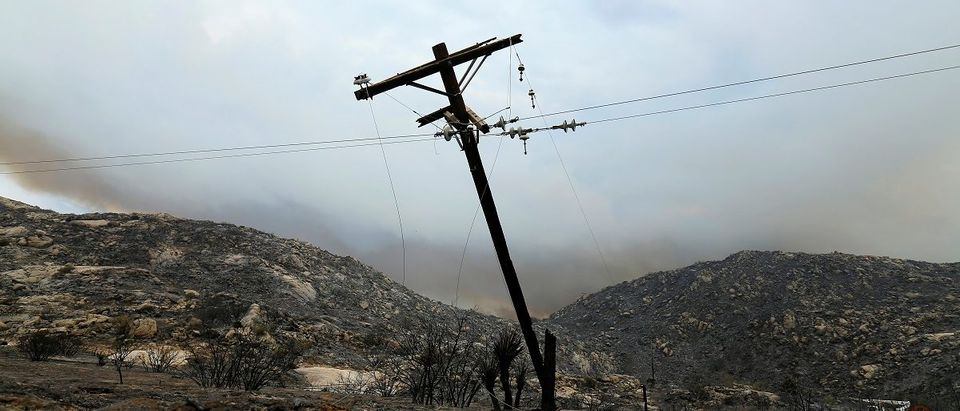 Utility workers begin work repairing power and data lines after a wildfire near Potrero