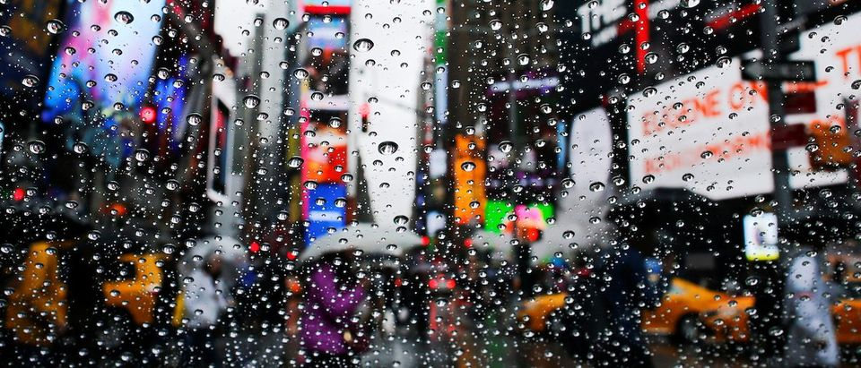 People walk under the rain on Times Square