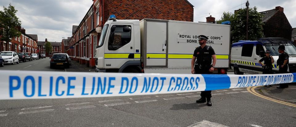 A bomb disposal unit and police officers wait behind cordon outside an address in Moss Side, Manchester