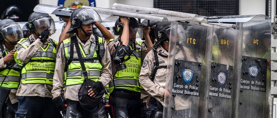 Riot police take cover behind their shields assuming a Romans-like tortoise formation as they clash with opposition activists during a protest against the government in Caracas on May 12, 2017. Daily clashes between demonstrators -who blame elected President Nicolas Maduro for an economic crisis that has caused food shortage- and security forces have left 38 people dead since April 1. Protesters demand early elections, accusing Maduro of repressing protesters and trying to install a dictatorship. (PHOTO: AFP/Getty Images/JUAN BARRETO)