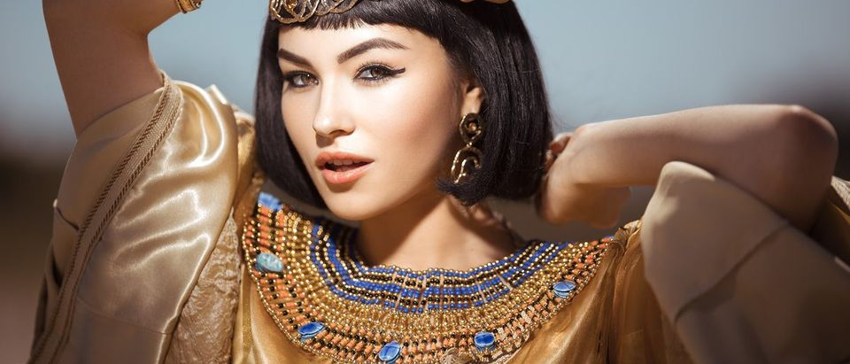 Photo of gorgeous woman with Cleopatra makeup, closeup portrait of beautiful female with stylish haircut agaist, young lady wearing fashionable golden necklace and holding magik ball outdoor, beauty