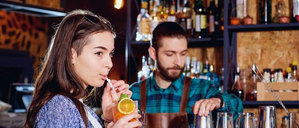 Woman drinks beverage with straw (Shutterstock/Studio Romantic)