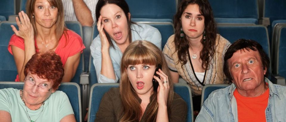 Loud woman on phone annoys audience in theater. [Shutterstock - CREATISTA]