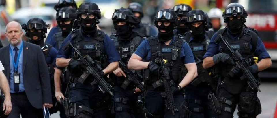 Armed police officers walk outside Borough Market after an attack left 6 people dead and dozens injured in London