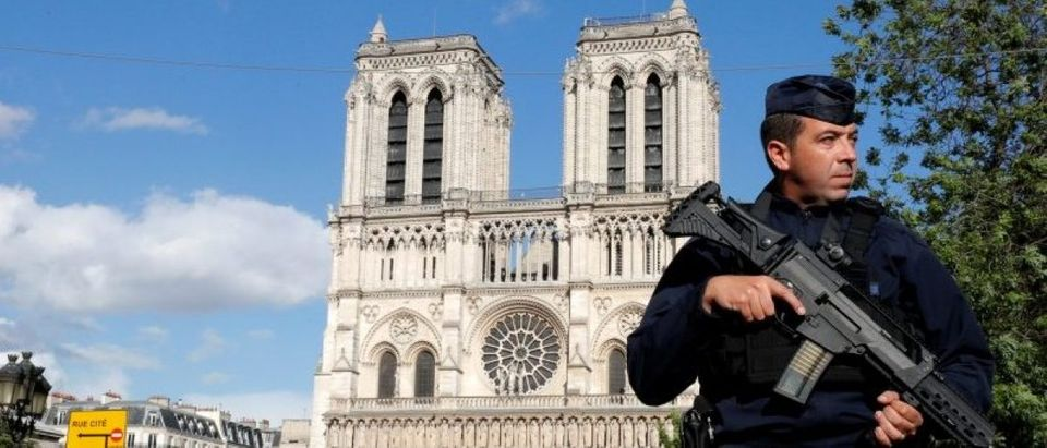 French police and gendarmes stand at the scene of a shooting incident near the Notre Dame Cathedral in Paris