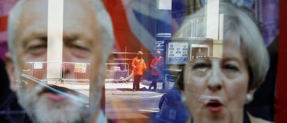 Wokers are reflected in the window of a betting shop with a display inviting customers to place bets on tbe result of the general election with images of Britain's Prime Minister Theresa May and opposition Labour Party leader Jeremy Corbyn, in London
