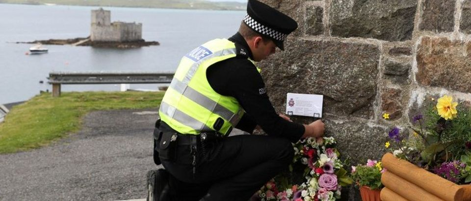 Flowers are laid by an officer from Police Scotland outside the Church of Our Lady, Star of the Sea, ahead of the funeral of Manchester bomb victim Eilidh MacLeod, in Castlebay on the island of Barra