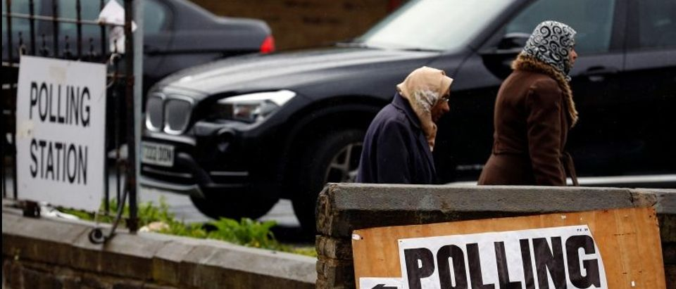 Voters walk past a polling station in Bradford