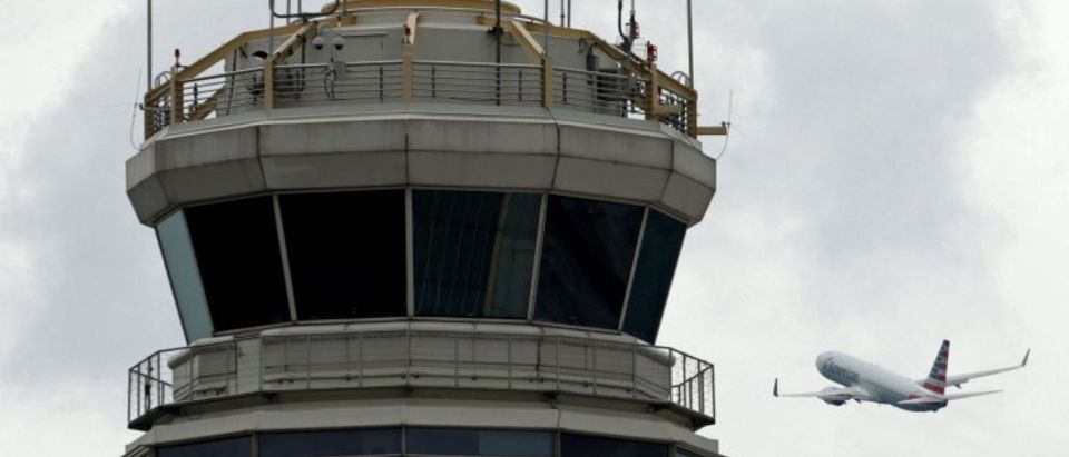 FILE PHOTO - A plane passes the air traffic control tower at Ronald Reagan Washington National Airport in Arlington