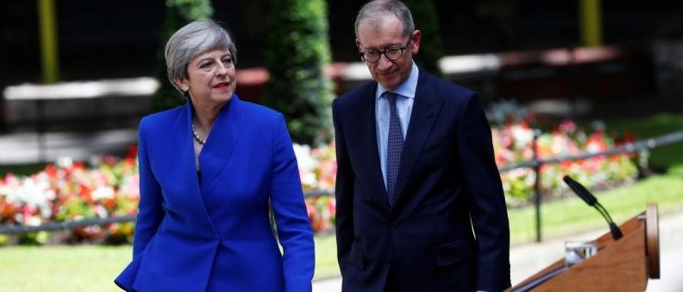Britain's Prime Minister Theresa May returns to Downing Street with her husband Philip after traveling to Buckingham Palace to ask the Queen's permission to form a minority government, in London