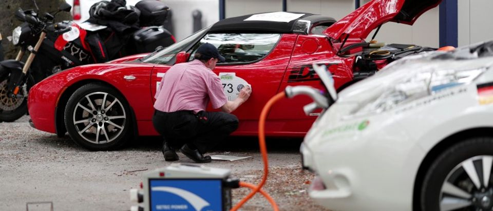 A man prepares his Tesla Roadster electric car at he world's biggest electric vehicle rally, the WAVE Trophy, in Zurich