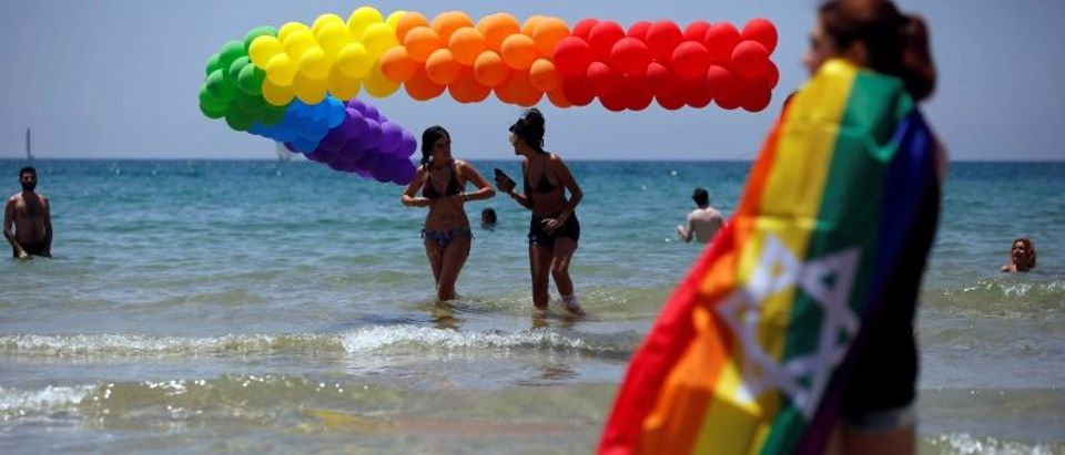 Revellers dip in the Mediterranean sea as they take part in a gay pride parade in Tel Aviv