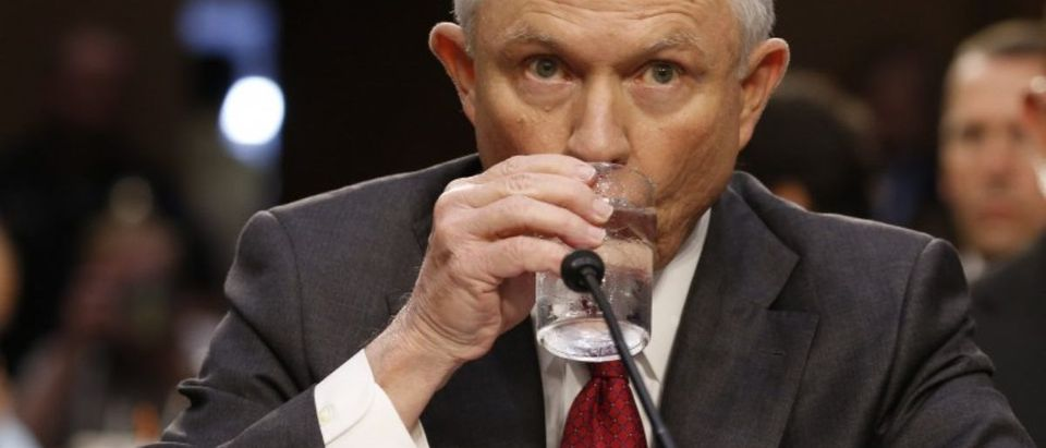 U.S. Attorney General Sessions takes a drink prior to testifying before a Senate Intelligence Committee hearing on Capitol Hill in Washington