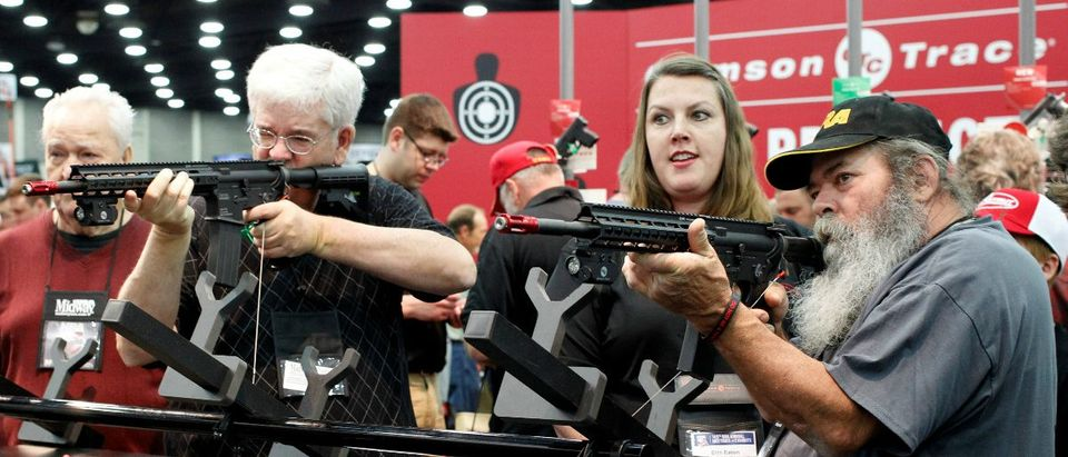 Gun enthusiasts test out laser sights at Crimson Trace Corp. at the National Rifle Association's (NRA) annual meetings and exhibits show in Louisville, Kentucky, May 21, 2016. REUTERS/John Sommers II
