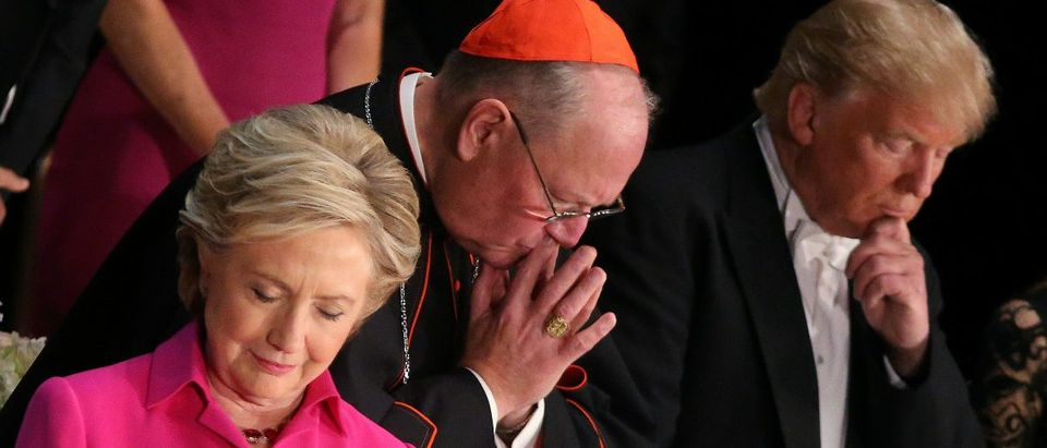 Democratic U.S. presidential nominee Hillary Clinton, Archbishop of New York Cardinal Timothy Dolan and Republican U.S. presidential nominee Donald Trump pray as they attend the Alfred E. Smith Memorial Foundation dinner to benefit Catholic charities in New York, U.S. October 20, 2016. REUTERS/Carlos Barria